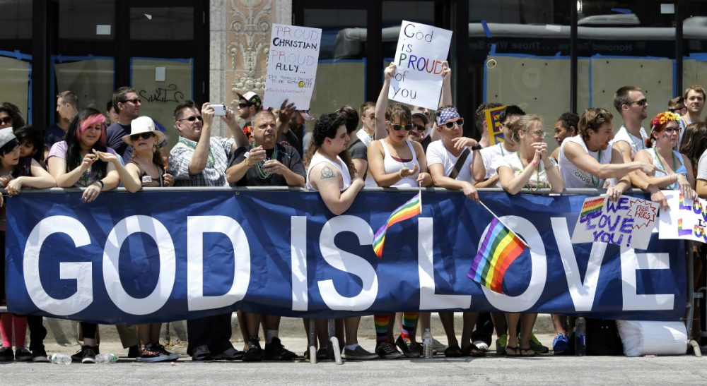 On this Bisexual Awareness Day, considering the role that faith communities can -- and should -- play in welcoming believers of all sexualities. Pictured: People stand behind a banner during the annual Chicago Pride Parade on Sunday, June 28, 2015, in Chicago. (Nam Y. Huh/AP)