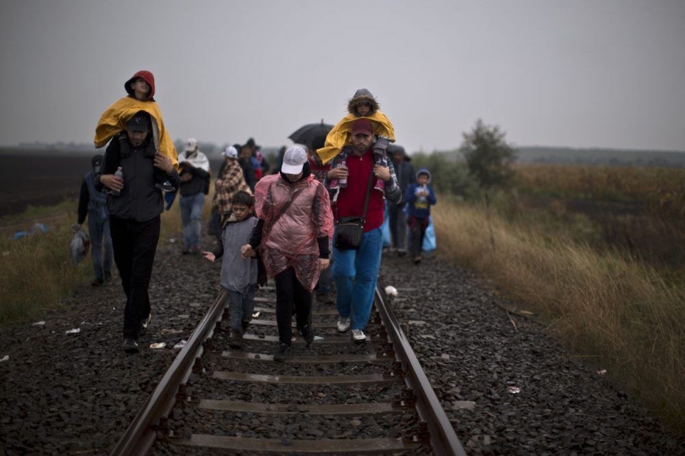 Syrian refugees walk on a railway track toward a makeshift camp for asylum seekers in southern Hungary Thursday. (Muhammed Muheisen/AP)