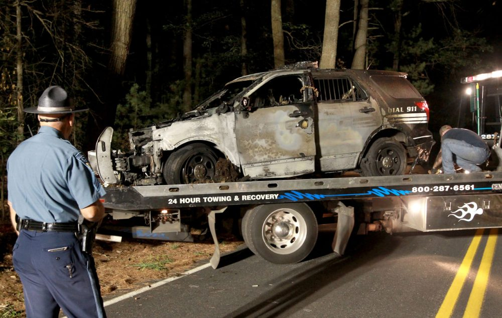 A cruiser that was shot at and burned is removed from Forest Road in Millis last week. Police say Officer Bryan Johnson shot at his own cruiser and fabricated a suspect description. (John Blanding/The Boston Globe via AP, Pool)