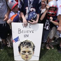 """Garry Emmons: """"If people applied the same intelligent scrutiny and research to public policy questions as they did to sports, would Team USA be doing a whole lot better?"""" Pictured: New England Patriots fans stand behind a sign supporting quarterback Tom Brady during an NFL football training camp in Foxborough, Mass., in July, 2015. A federal judge deflated """"Deflategate"""" Thursday, Sept. 3, 2015.  (Charles Krupa/AP)"""