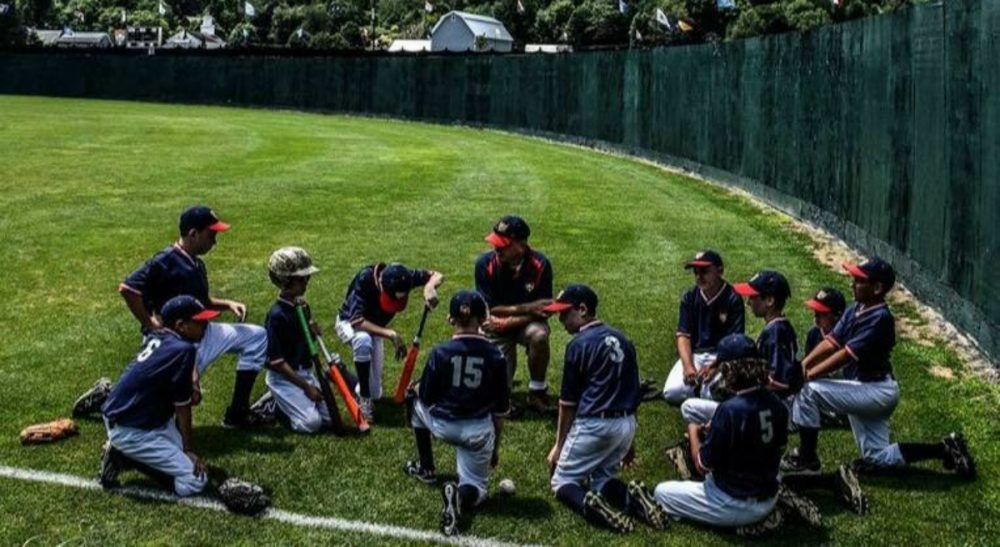 "Ted Flanagan: ""In the hills outside of Cooperstown this past July, 11 boys reminded me that there is still joy to be had in picking up the lance and jousting at windmills. There's more than one way to be built to win."" Pictured: The author and the Lions talk strategy in right field before a game in July, 2015, at the annual Cooperstown Dreams Park Tournament. (Alex Belisle/Courtesy)"