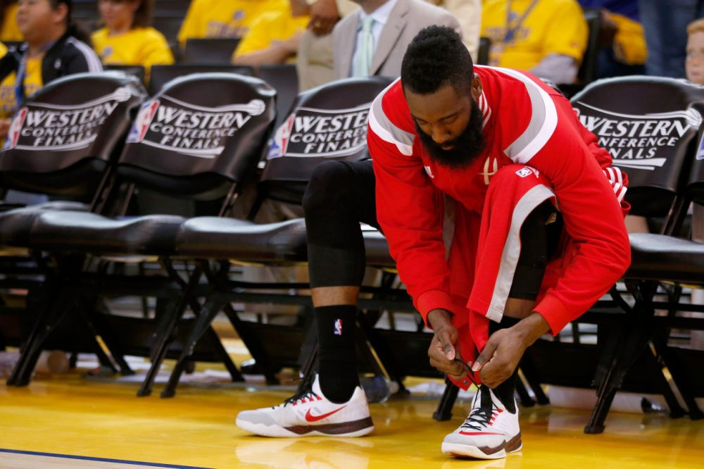 1ce520cb2e95 Houston Rockets gaurd James Harden laces up his Nike sneakers in  preparation for a game last