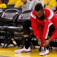 Houston Rockets gaurd James Harden laces up his Nike sneakers in preparation for a game last season.  He'll be donning a different pair when the season opens in October.