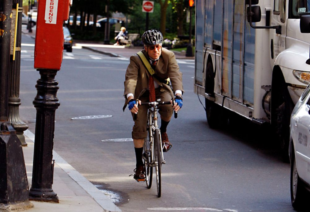 A man rides a bicycle on his morning work commute through downtown Boston, sharing the road with trucks and cars. (AP Photo/Bizuayehu Tesfaye)