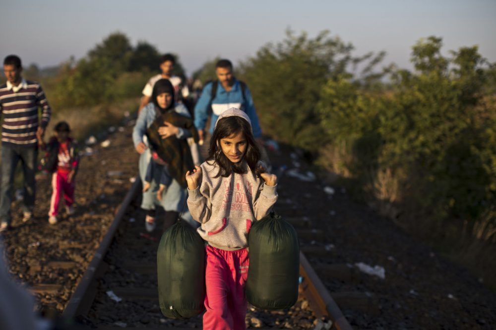 Syrian refugees make their way on a railway track after crossing the border between Serbia and Hungary in Roszke, southern Hungary. Many migrants are searching for another country to resettle in. (AP Photo/Muhammed Muheisen)