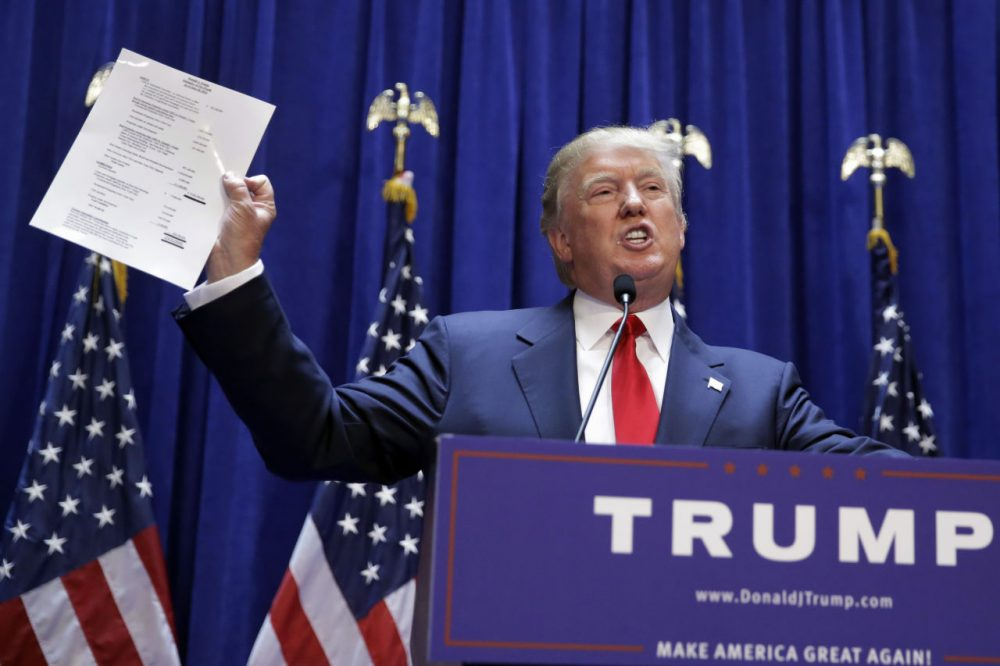 Developer Donald Trump displays a copy of his net worth during his announcement that he will seek the Republican nomination for president, Tuesday, June 16, 2015, in the lobby of Trump Tower in New York. (AP Photo/Richard Drew)
