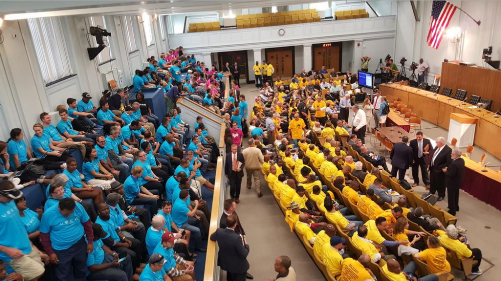 Uber drivers in blue, taxi drivers in yellow, and Lyft drivers in pink packed into the Gardner Auditorium to hear four bill proposals on ride-hailing companies. (Courtesy of Gintautas Dumcius)