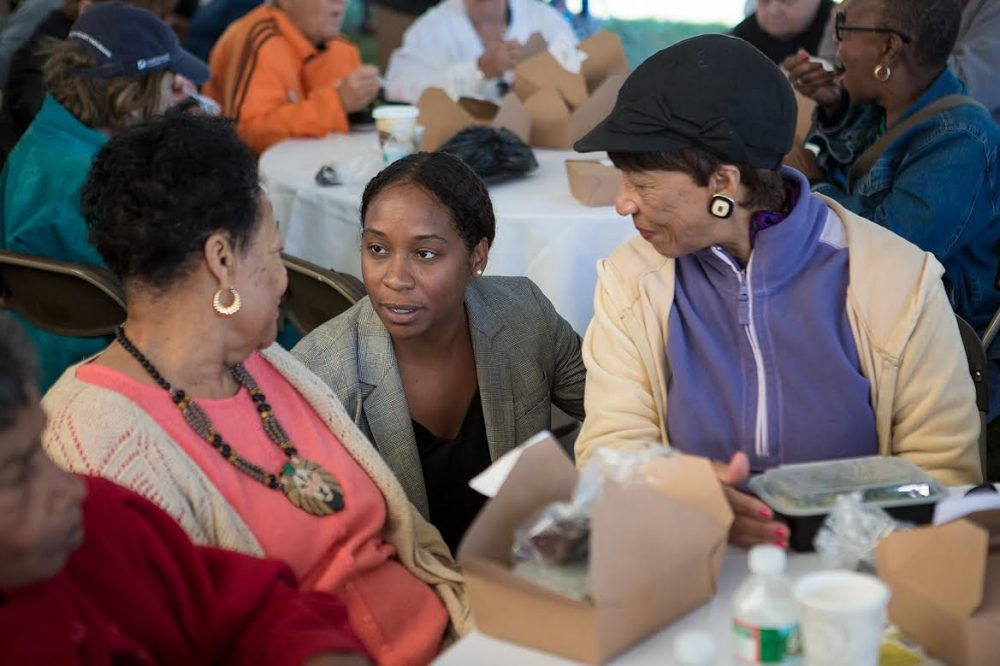 Andrea Campbell, center, spoke with seniors at a cookout in Boston's Harambee Park Wednesday. She's attempting to unseat Councilor Charles Yancey. (Jesse Costa/WBUR)