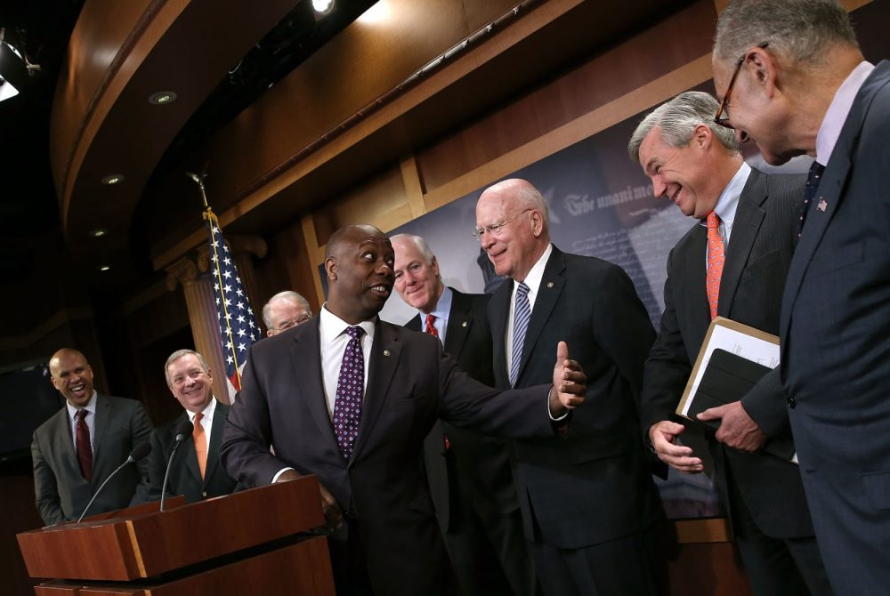 Sen. Tim Scott (C) (R-SC) jokes with Democratic senators including Sen. Sheldon Whitehouse (2nd R) (D-RI) during a press conference at the U.S. Capitol announcing a bipartisan effort to reform the criminal justice system. (Win McNamee/Getty Images)