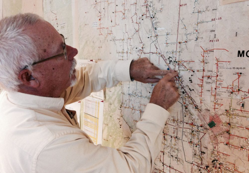 Steve Metheny of the Delta-Montrose Electric Association illustrates the utility's back-up to the back-up: a floor to ceiling paper map of their service area and infrastructure. (Jordan Wirfs-Brock/Inside Energy)