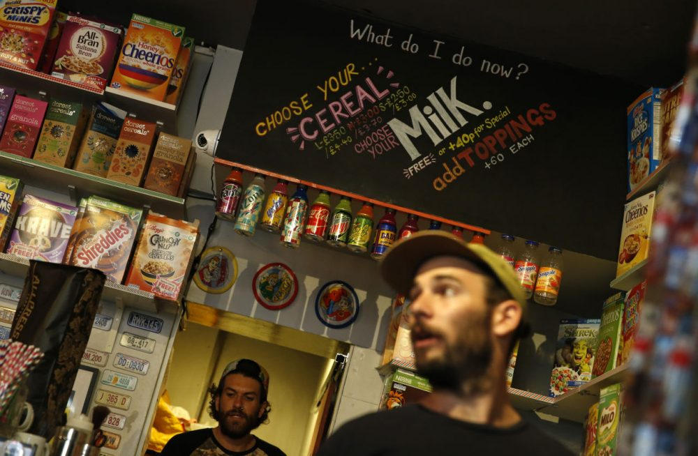 """A member of staff of the Cereal Killer Cafe helps point out to a customer the range of cereals available, from U.S. favorites to European gluten free organics, at the cafe in Brick Lane, London, Wednesday, Sept. 30, 2015. The Cereal Killer Cafe has drawn both derision and big crowds since it opened nine months ago, offering a cornucopia of flakes, pops and puffs from about 3 pounds ($4.50) a bowl. Now it has attracted the ire of anti-gentrification protesters, who last week surrounded the business with flaming torches and scrawled """"scum"""" on its windows as customers sheltered in the basement. (Alastair Grant/AP)"""