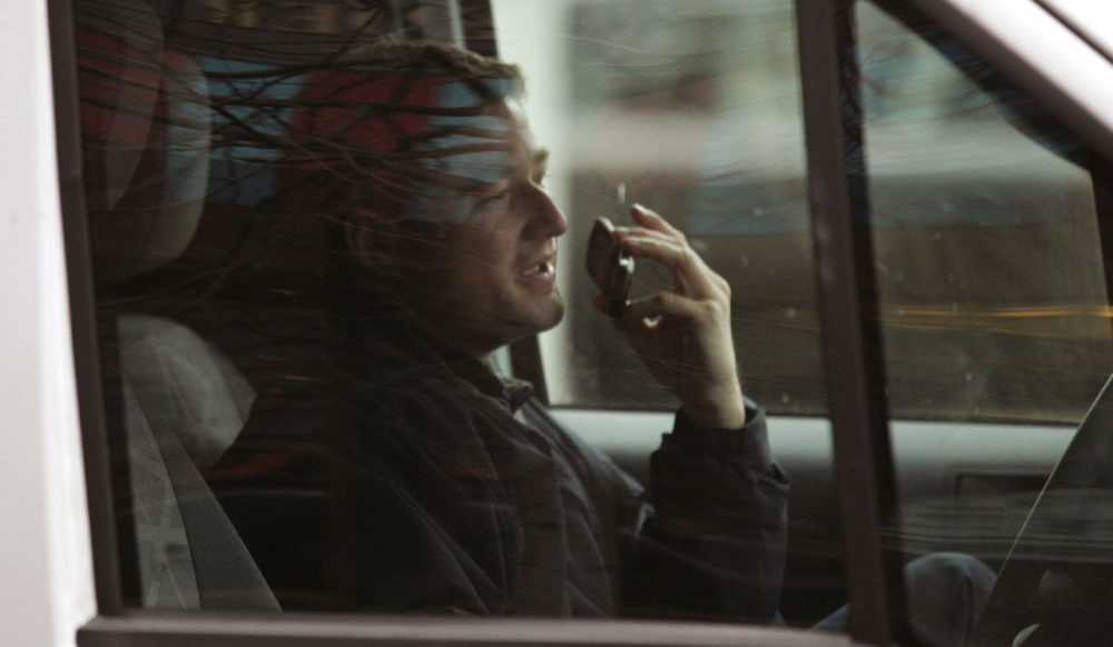 A driver talks on a cell phone while driving through the Financial District of Boston in 2011. The use of cellphones while driving has long been a source of contention in the state. Gov. Baker said he'd support a proposal to ban handheld use while driving. (Charles Krupa/AP)