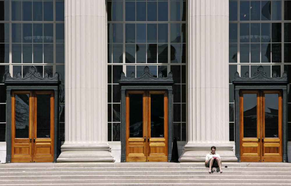 A doctoral student at MIT reads outside a building at the Cambridge campus. (Michael Dwyer/AP File)