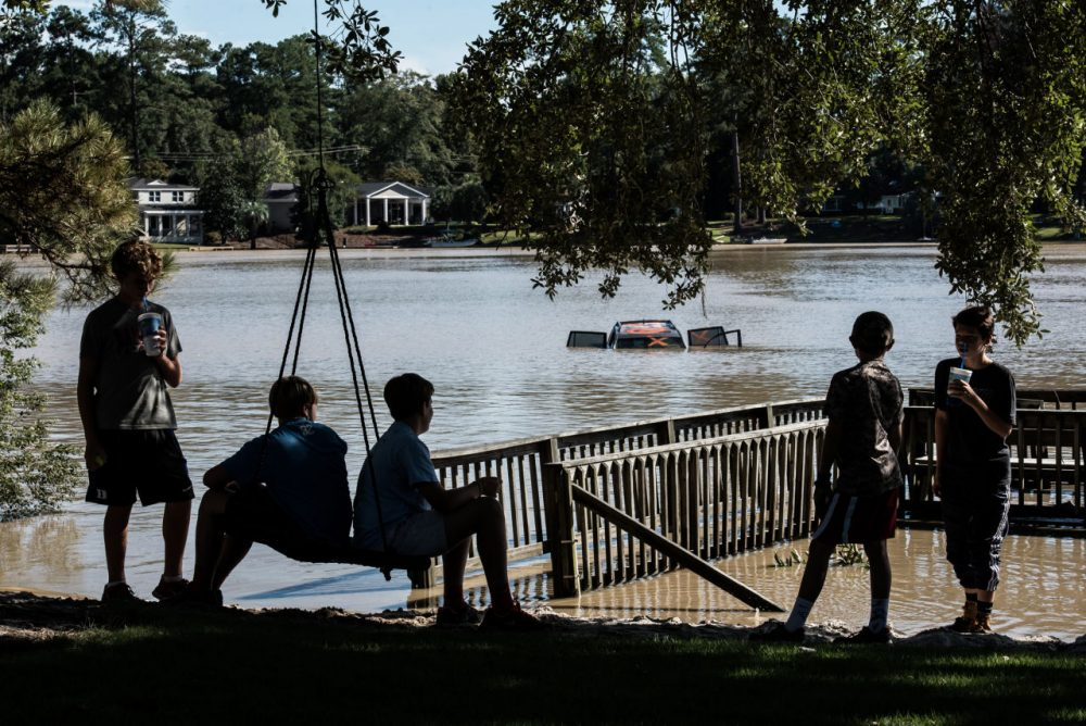 Children take a break from cleaning up a home in the Forest Acres neighborhood October 6, 2015 in Columbia, South Carolina. The state of South Carolina experienced record rainfall amounts over the weekend and officials expect the costs to be in the billions. (Sean Rayford/Getty Images)