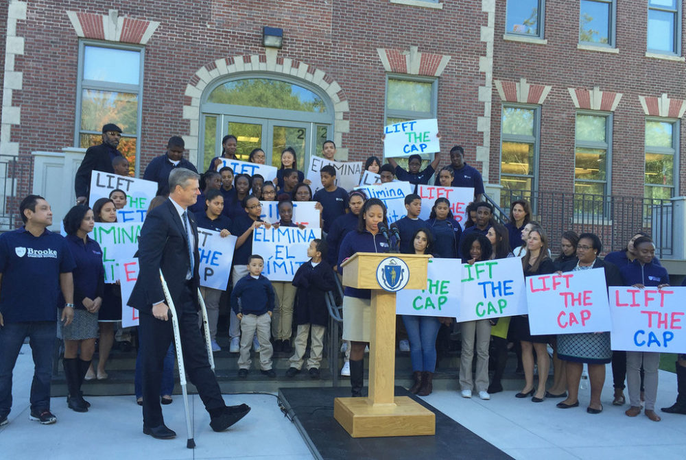 Gov. Charlie Baker, flanked by several schoolchildren holding signs, walks to announce proposed legislation on charter school caps. (Delores Handy/WBUR)