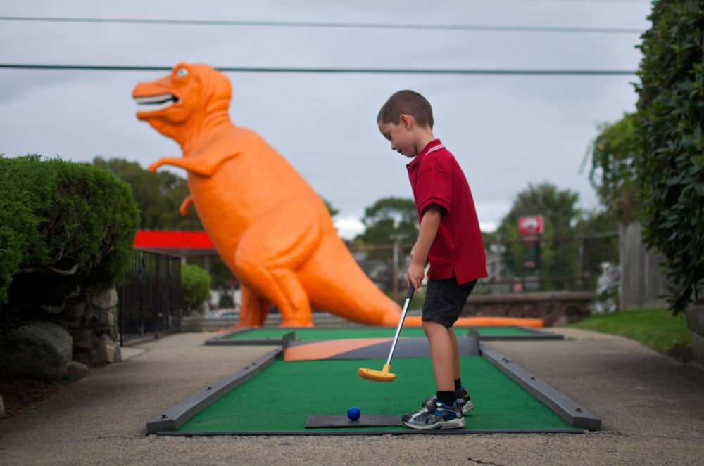 After more than 50 years, the old-fashioned miniature golf course off Route 1 in Saugus is closing. The spot is well known for its dayglo orange T-rex that, from the sixth hole, gazes over the highway. Here, Louie Schraffa, 5, of East Boston, prepares for a putt on the dinosaur hole. (Sharon Brody/WBUR)
