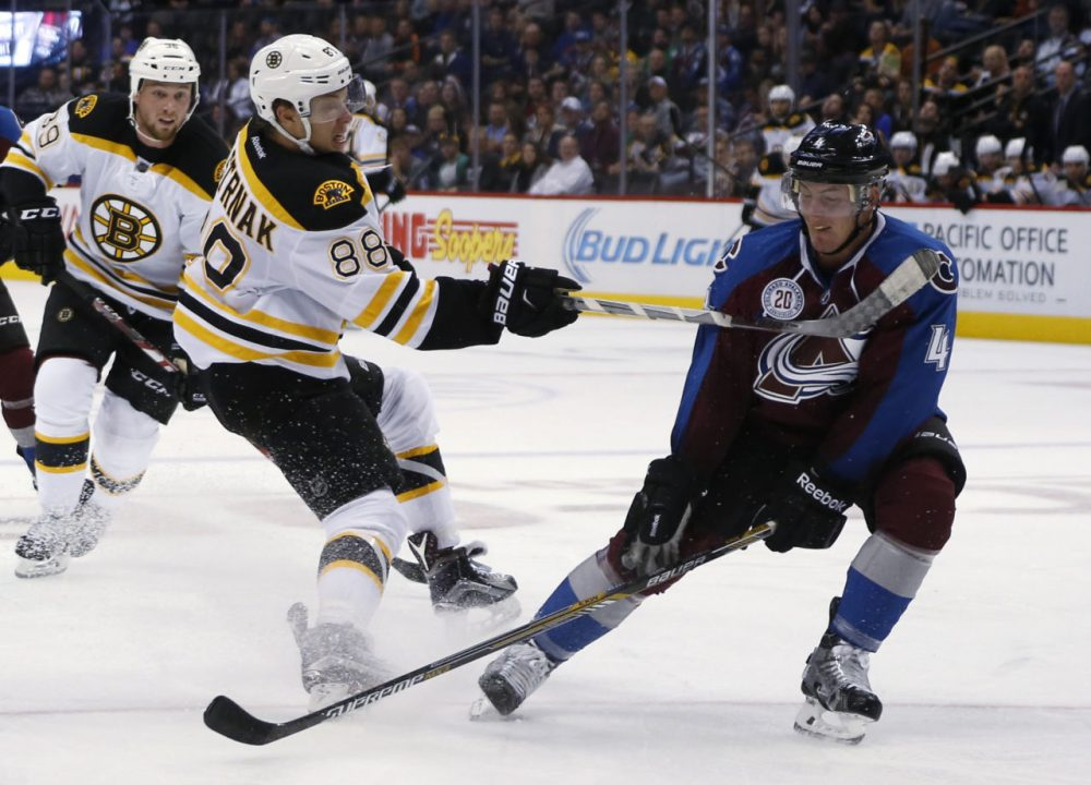Boston Bruins left wing David Pastrnak, left, of the Czech Republic, shoots past Colorado Avalanche defenseman Tyson Barrie during the game last night in Denver. (David Zalubowski/AP)