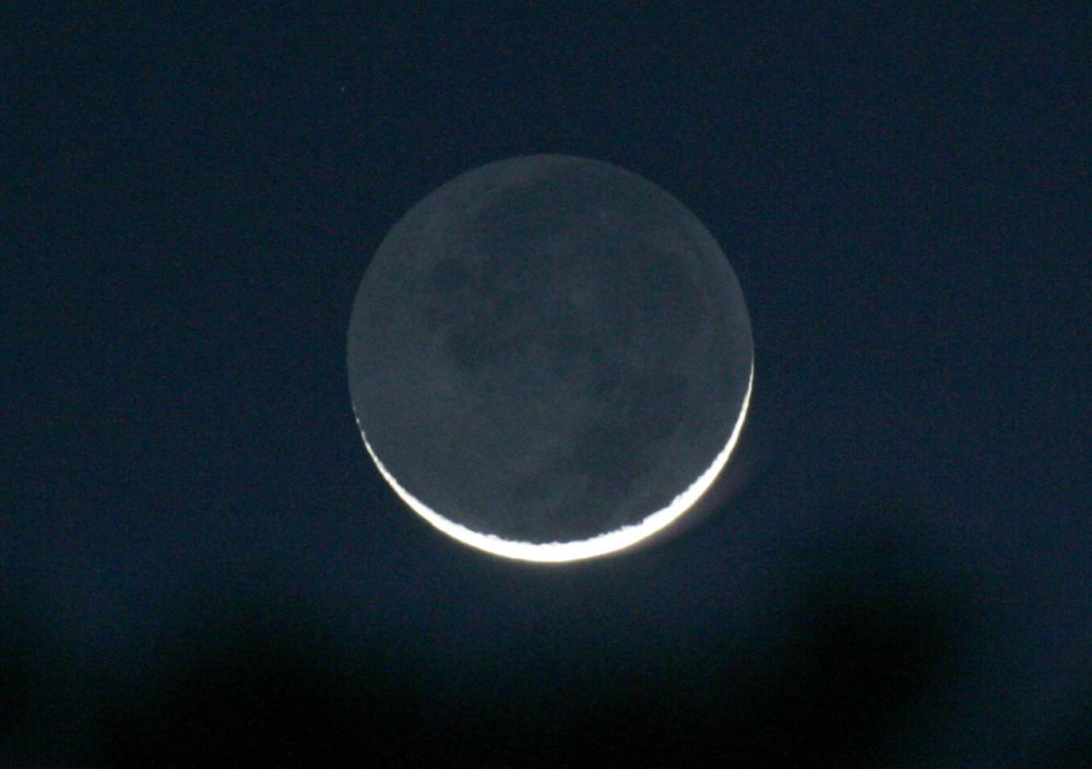 A thin waxing crescent moon is seen just after sunset, in Tyler, Texas on Friday, Feb. 8, 2008. The nightside of the moon is lit by reflected light from the dayside of the earth and is known as earthshine. (Dr. Scott M. Lieberman/AP)