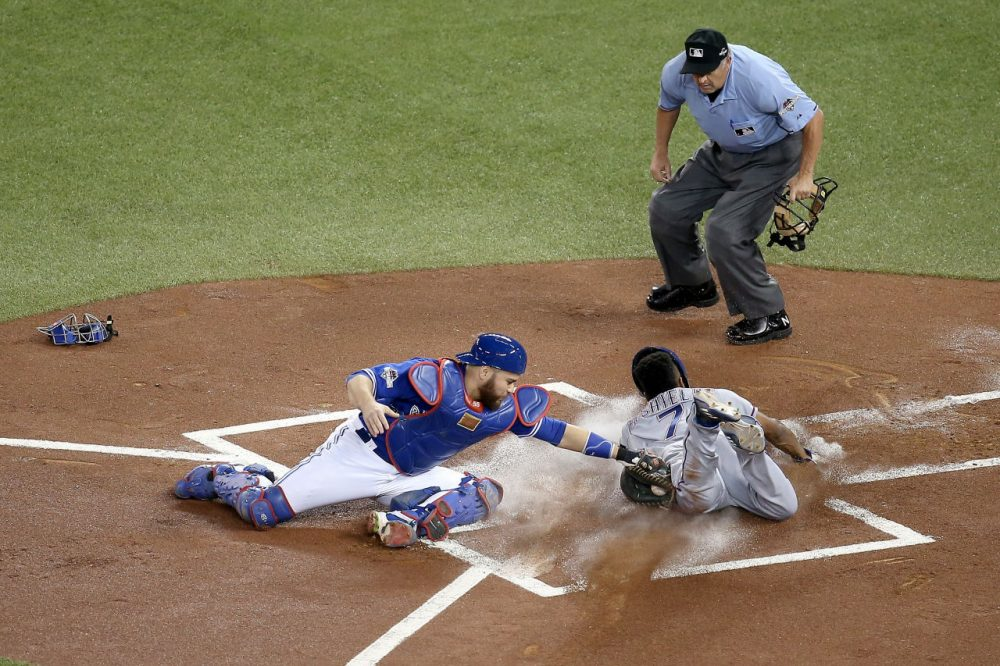 Delino DeShields #7 of the Texas Rangers slides into home safely ahead of the tag by Russell Martin #55 of the Toronto Blue Jays in the first inning against the Toronto Blue Jays in game five of the American League Division Series at Rogers Centre on October 14, 2015 in Toronto, Canada. (Tom Szczerbowski/Getty Images)
