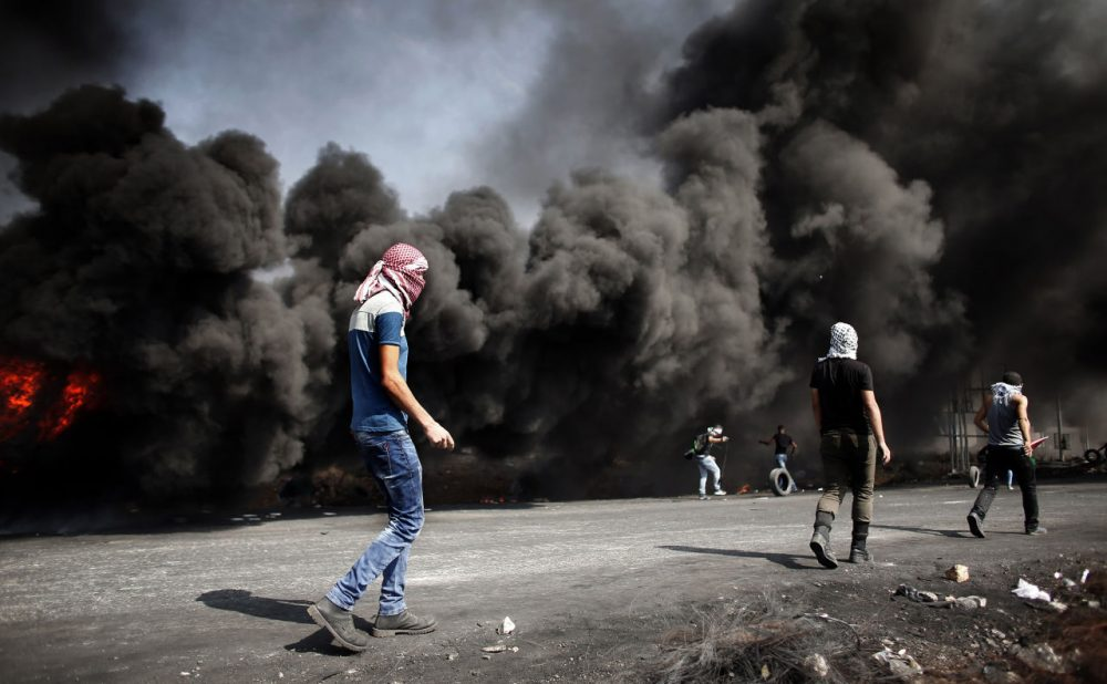 Palestinian demonstrators gather behind burning tires to throw stones towards Israeli security forces during clashes in the West Bank town of Al-Bireh, on the northern outskirts of Ramallah, on October 20, 2015.  (Thomas Coex/AFP/Getty Images)