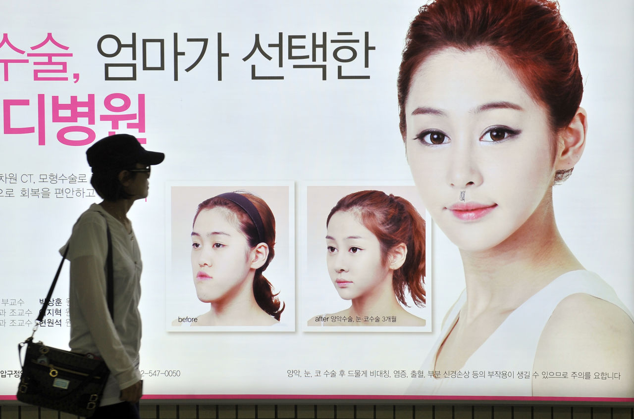 This picture taken on May 22, 2013 shows a South Korean woman walking past a street billboard advertising double-jaw surgery at a subway station in Seoul. South Korea's obsession with plastic surgery is moving on from standard eye and nose jobs to embrace a radical surgical procedure that requires months of often painful recovery. (Jung Yeon-Je/AFP/Getty Images)