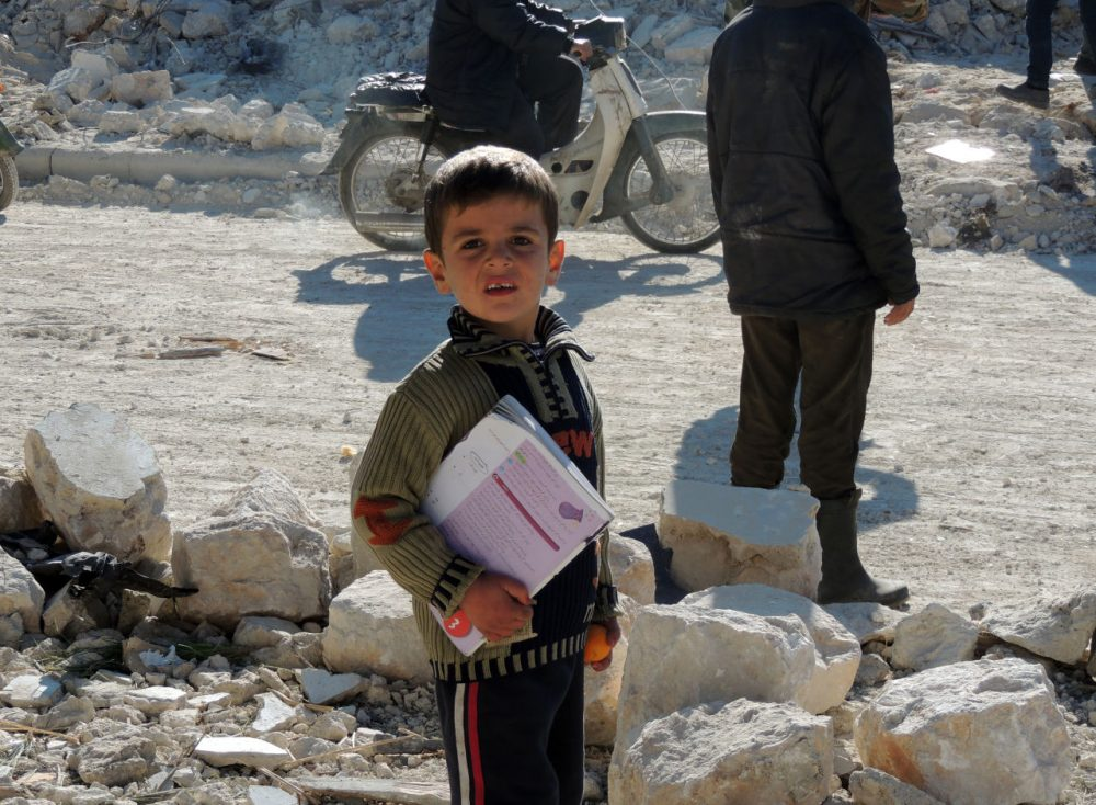 A Syrian boy holds books as he stands outside his school following airstrikes by Syrian government forces on December 22, 2013 in the northern Syrian city of Marea on the outskirts of Aleppo. (Mohammed Al-Khatieb/AFP/Getty Images)