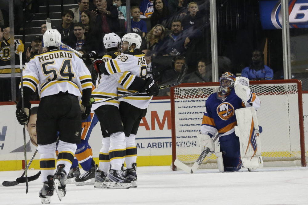 New York Islanders goalie Jaroslav Halak, right, reacts as Boston Bruins left wing David Pastrnak (88) celebrates with teammates after scoring a goal during the game's second period Friday in New York. (Mary Altaffer/AP)