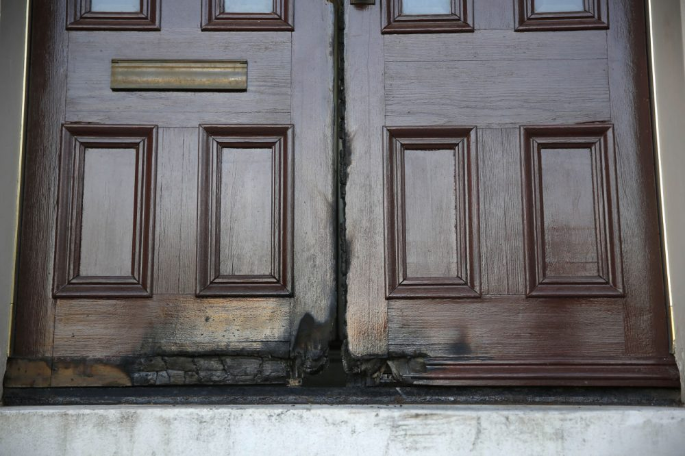 Fire-damaged rectory doors at the 173-year-old Shrine of St. Joseph church that were damaged by an arsonist are shown Thursday, Oct. 22, 2015, in St. Louis. The fire, set early Thursday morning, marks the seventh time in two weeks someone ignited doors outside a place of worship in St. Louis or one of its suburbs, police said. (Jeff Roberson/AP)