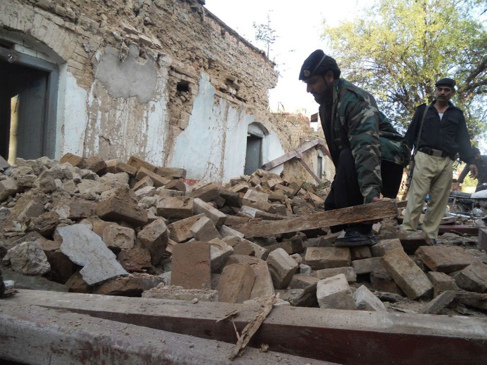 A Pakistani policeman digs through the debris of collapsed houses after an earthquake in Kohat on October 26, 2015. A powerful 7.5 magnitude earthquake killed at least 70 people as it rocked south Asia, including 12 Afghan girls crushed to death in a stampede as they tried to flee their collapsing school. (Basit Shah/AFP/Getty Images)
