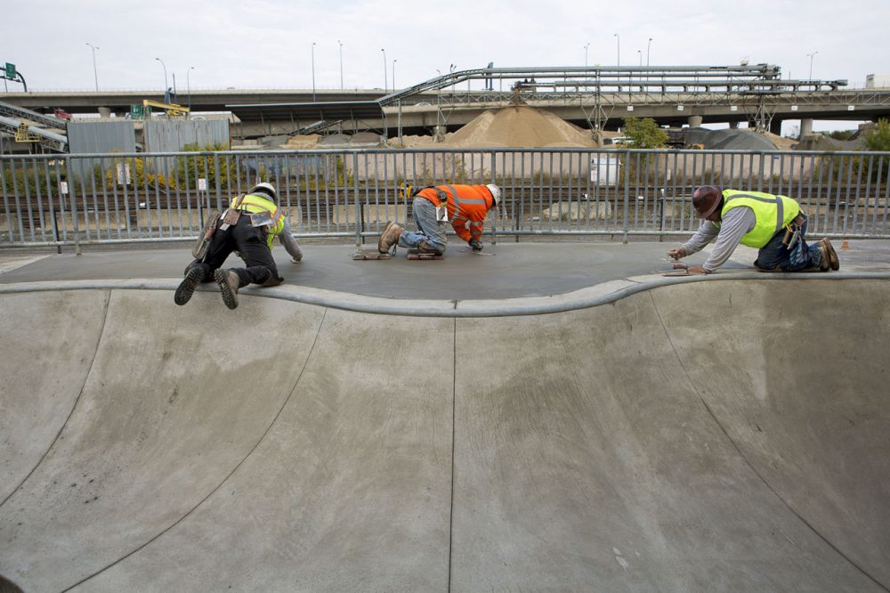 After more than a decade of planning, the Lynch Family Skatepark will open in November, giving local skaters a large scale place to skate. Pictured: Workers laid cement for the skate park in Cambridge. (Jesse Costa/WBUR)