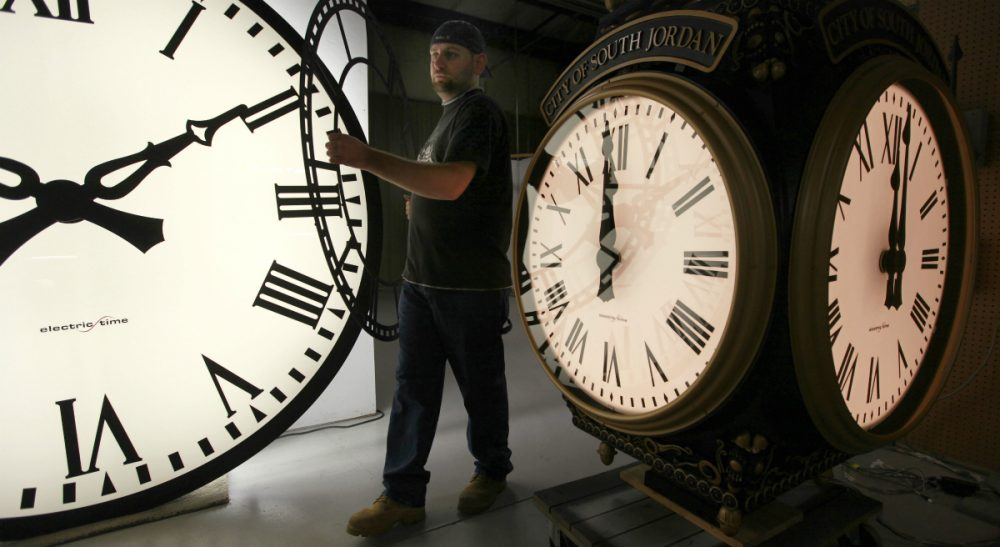 In this 2011 photo, Dan LaMoore of Electric Time Company moves a clock face at their plant in Medfield, Mass., between a large tower clock and a post clock. Daylight Savings Time ends at 2 a.m. on Sunday, Nov. 1, 2015, when clocks will be set back one hour. (Elise Amendola/AP)