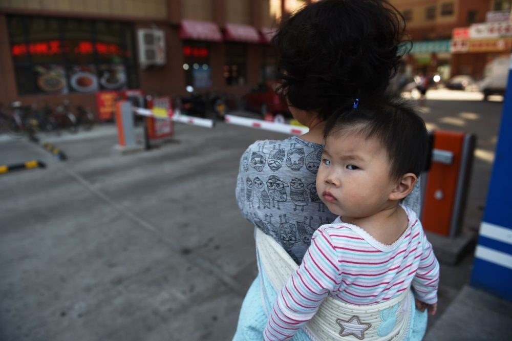 A woman carrying a baby in Yanji, in China's northeast Jilin province. China's Communist leaders gather on October 26 to hash out a new Five Year Plan to battle slowing growth, and analysts say they must choose between such outmoded concepts as GDP targets and reforms that could include the one-child policy.   (Greg Baker/AFP/Getty Images)