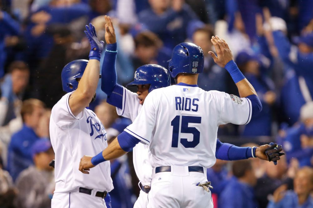 Alcides Escobar #2 of the Kansas City Royals and Alex Rios #15 of the Kansas City Royals celebrate with Kendrys Morales #25 of the Kansas City Royals after scoring runs in the fifth inning against the New York Mets in Game Two of the 2015 World Series at Kauffman Stadium on October 28, 2015 in Kansas City, Missouri. (Sean M. Haffey/Getty Images)