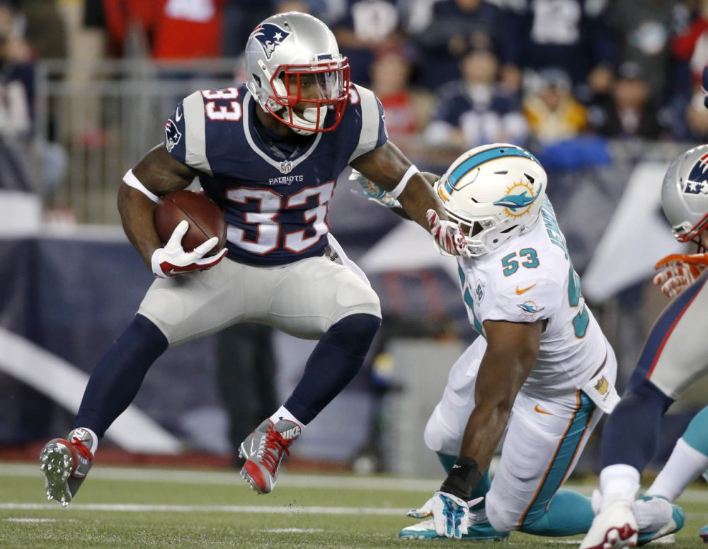 Patriots running back Dion Lewis (33) evades Miami Dolphins outside linebacker Jelani Jenkins (53) in Thursday night's game. (Michael Dwyer/AP)