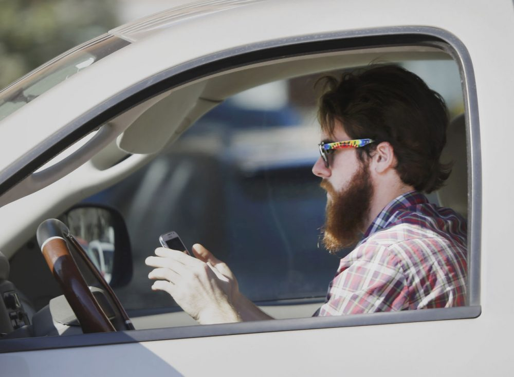An man works his phone as he drives through traffic. (LM Otero/AP)