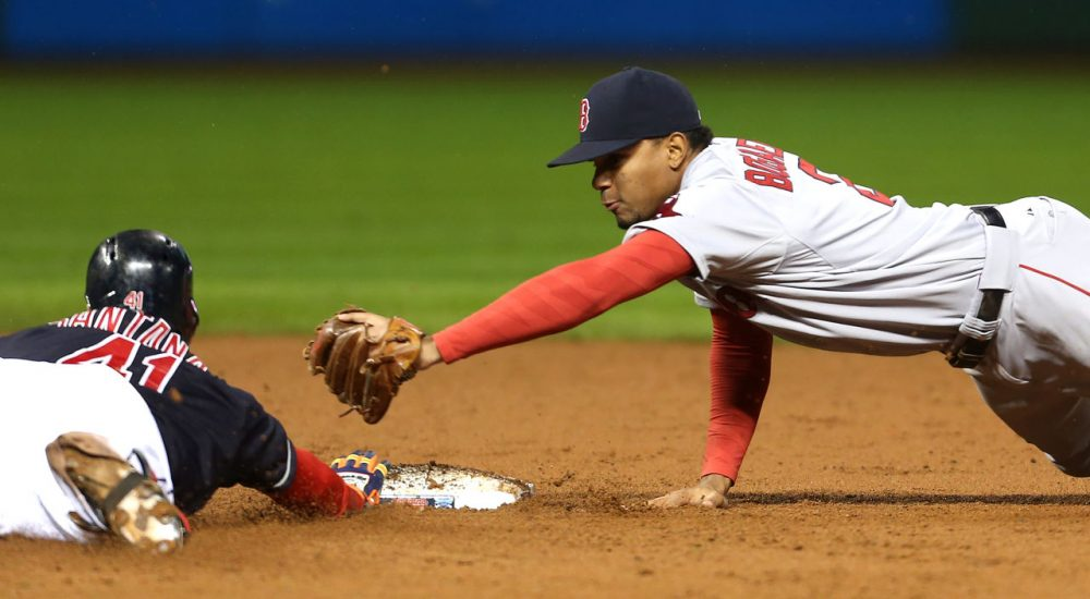 Cleveland Indians' Carlos Santana slides safely into second base with a double as Boston Red Sox's Xander Bogaerts attempts to make the tag during the eighth inning of a baseball game (Ron Schwane/AP Photo)