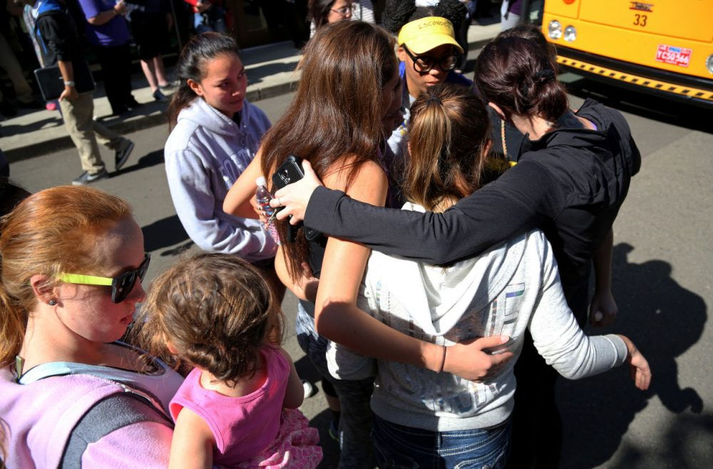 Friends and family are reunited with students at the local fairgrounds after a deadly shooting at Umpqua Community College in Oregon Thursday. (Ryan Kang/AP)