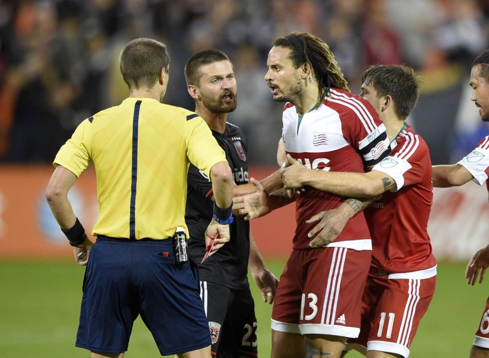 Revolution midfielder Jermaine Jones (13) is restrained after he was given a red card and ejected during the second half of an MLS playoff game Wednesday in Washington. D.C. United won 2-1. (Nick Wass/AP)