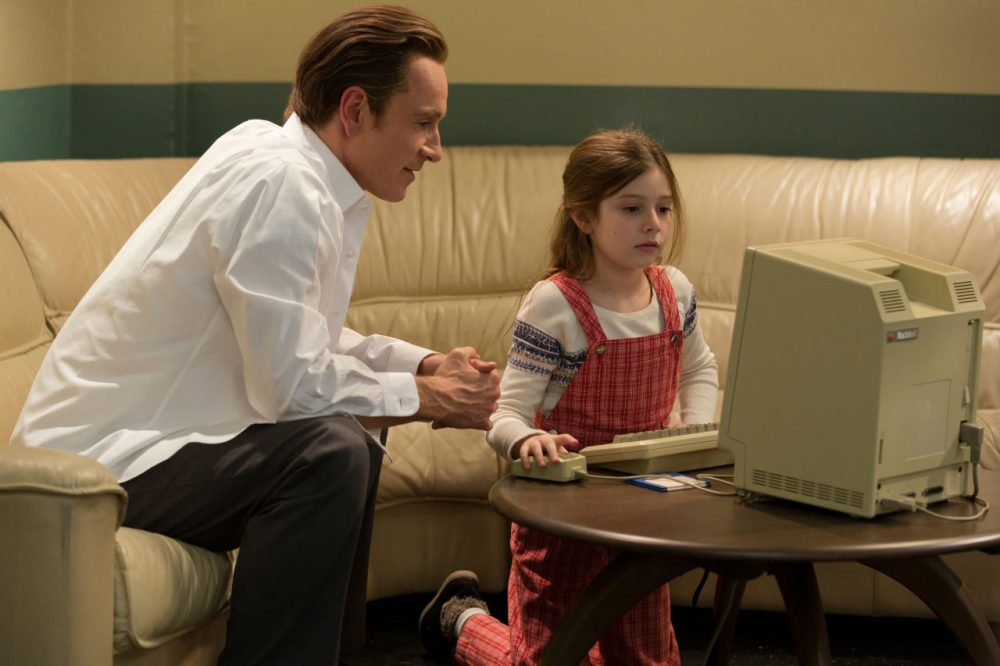 """Michael Fassbender, left, as Steve Jobs and Makenzie Moss as a young Lisa Jobs, appear in a scene from the film, """"Steve Jobs."""" The movie releases in the U.S. on Friday, Oct. 9, 2015. (Francois Duhamel/Universal Pictures via AP)"""