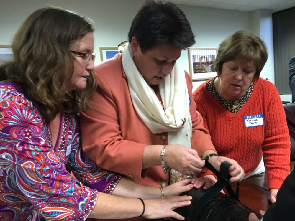 Nurses Bridget Jaklitsch (left) and Theresa Hartel (right) hold a dummy thigh in place as Elizabeth Paquette (center) threads the buckle on a tourniquet at a training session on stopping severe bleeding at the Archdiocese of Boston headquarters in Braintree. (Martha Bebinger/WBUR)