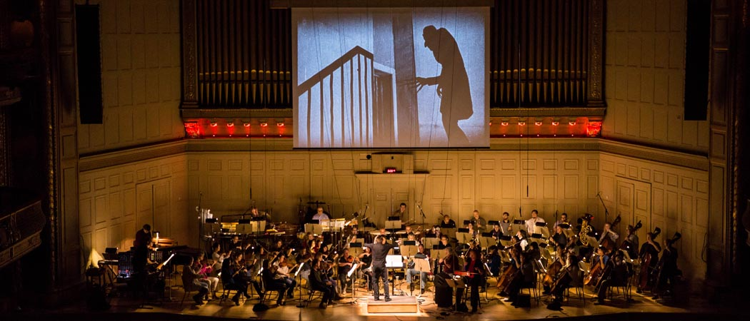 """The Boston Pops rehearse a score created by Berklee College of Music for the iconic 1922 silent film """"Nosferatu: A Symphony of Horror,"""" as the movie plays above the stage. (Courtesy Elizabeth Friar)"""