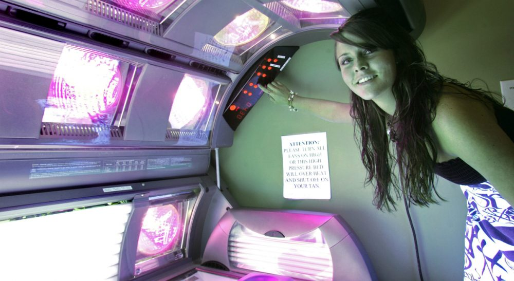 A 17-year-old -- who has been using tanning beds since she was 14 -- prepares a tanning bed for a session, Wednesday, March 25, 2009, in Tallahassee, Fla.  The Massachusetts House is now considering a bill to ban tanning bed use by minors. (Phil Coale/AP)
