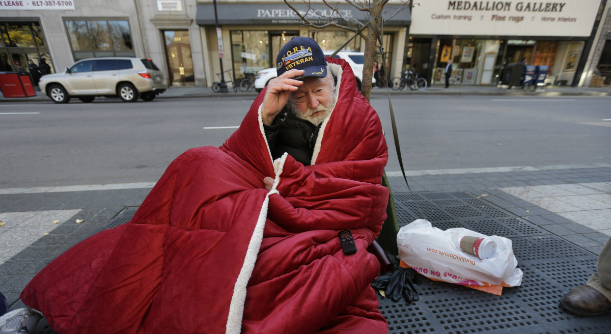 A homeless man adjusts his hat while wrapped in a blanket on a sidewalk on Boylston Street in Boston. In the year since the Long Island Bridge closure cut off access to a homeless shelter on the island, homelessness has risen 5.6 percent in Boston. (Steven Senne/AP)