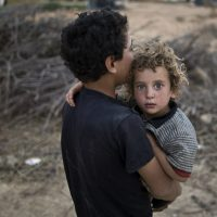 "John Tirman: ""These American wars contain an element of Greek tragedy, beginning with hubris and ending with an unconscious, Oedipal urge to blind ourselves to the horror of what we've done."" Pictured: A Syrian refugee boy carries his younger brother back to their tent at an informal tented settlement near the Syrian border on the outskirts of Mafraq, Jordan, Tuesday, Aug. 4, 2015. (Muhammed Muheisen/AP)"