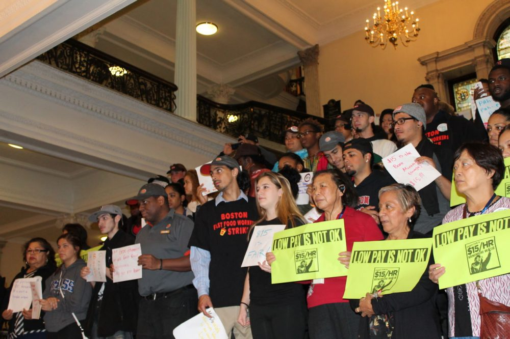Dozens of fast food workers rallied at the State House Tuesday to urge lawmakers to boost the minimum wage to $15 an hour by 2018 and to support bills they say would make scheduling fairer for employees. (Antonio Caban/SHNS)