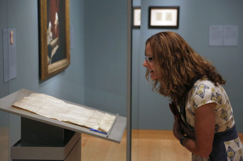 Museums are trying many new ways to get visitors into the galleries. A woman looks an original copy of the Magna Carta when it came to the MFA in Boston in 2014.  (AP Photo/Steven Senne)