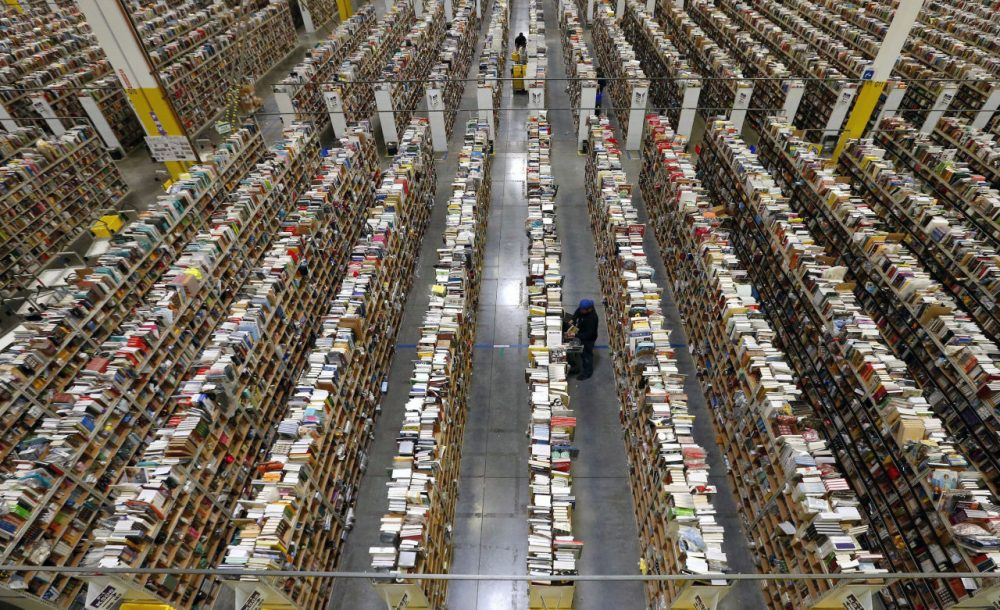 An Amazon.com employee stocks books along one of the many miles of aisles at an Amazon.com Fulfillment Center in Phoenix on December 2, 2013. Amazon just opened its first brick and mortar store in Seattle today. (Ross D. Franklin/AP Photo)