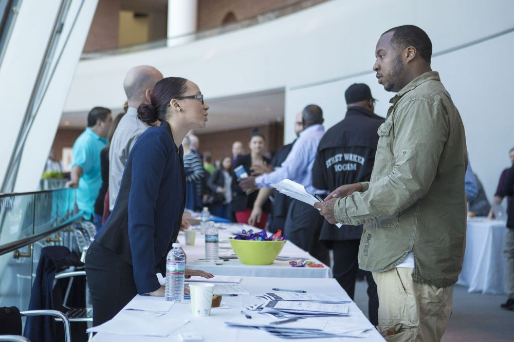 A former inmate inquires about job programs from one of the many vendors at a community resource fair at the Moakley courthouse in Boston Wednesday, hosted by the U.S. Probation and Pretrial Office. (Jesse Costa/WBUR)