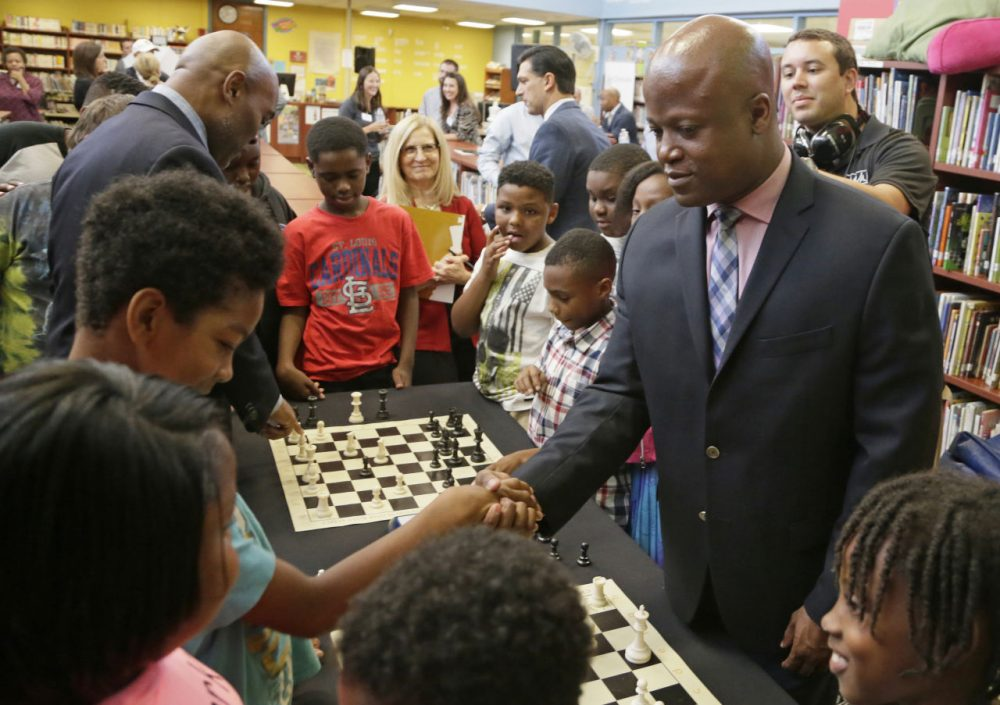Chess Grand Master Maurice Ashley, right, shakes the hand of his opponent, a student from Walnut Grove Elementary School, after defeating him in a friendly match at a news conference to announce an initiative by Ascension and the St. Louis Chess club to start chess clubs in the schools of the Ferguson-Florissant school district, Tuesday, Sept. 15, 2015 at Walnut Grove Elementary School in Ferguson, Missouri. (Tom Gannam/Invision for The Chess Club and Scholastic Center of St. Louis via AP)