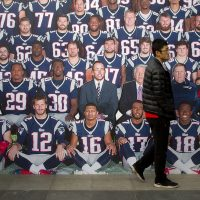 In this photo, a man walks past a life-sized team photo of the New England Patriots at a National Football League publicity event held in Beijing, Sunday, Nov. 8, 2015. The NFL has been aggressively promoting football in China hoping to take advantage of rising income and growing taste for exotic foreign sports. (Mark Schiefelbein/ AP)